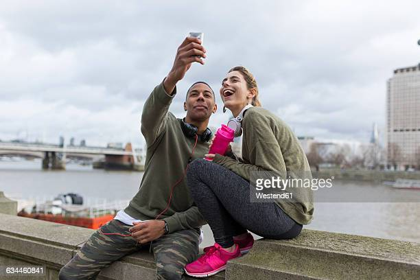 UK, London, two runners taking a selfie at riverwalk