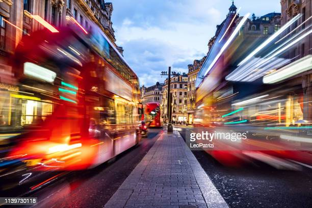 london typical red bus blurred motion at night in oxford circus - oxford street london stock pictures, royalty-free photos & images