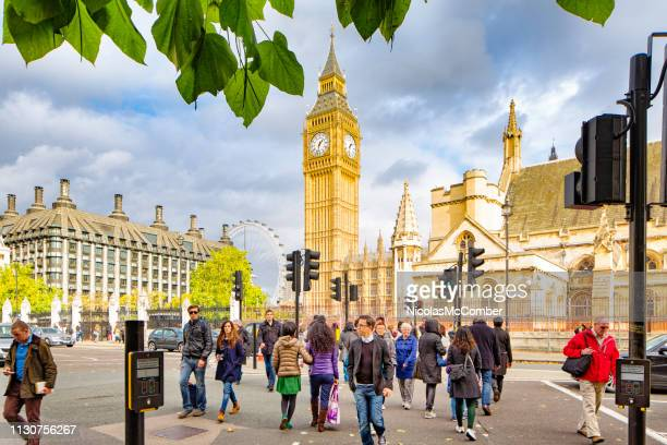 london uk real people crossing parliament street on a warm autumn day - westminster bridge stock pictures, royalty-free photos & images