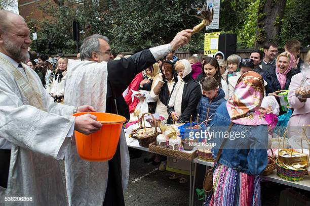 London UK Saturday 19th April 2014 Priest blesses the gathered people with a great deal of holy water Easter celebration gathering at the Russian...
