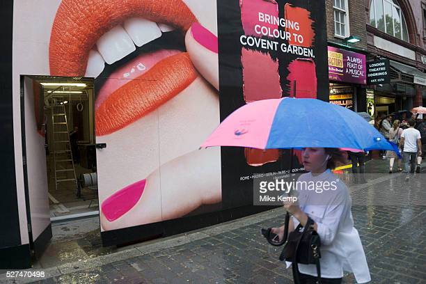 London, UK. Sunday 23rd August 2015. Heavy summer rain showers in the West End. People brave the wet weather armed with umbrellas and waterproof...