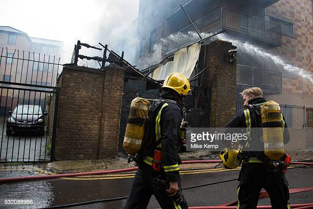 London UK Wednesday May 18th 2016 Fire fighters tackle a fire in a block of flats in Brodlove Lane in Wapping London United Kingdom According to...
