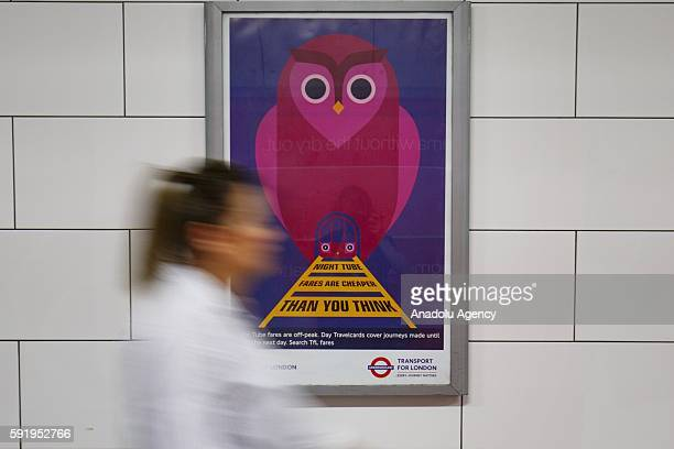 London Underground passengers walk past a new Night Tube poster at Oxford Circus station in London England on August 19 2016 Transport for London...
