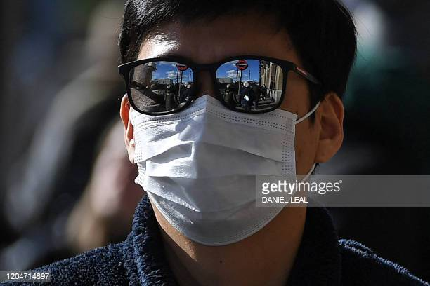 A London Underground sign is reflected in the sunglasses of a tourist wearing surgical face mask in central London on March 2 2020 Britain's Prime...