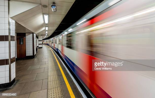 A London Underground train streaks by as it departs from the station