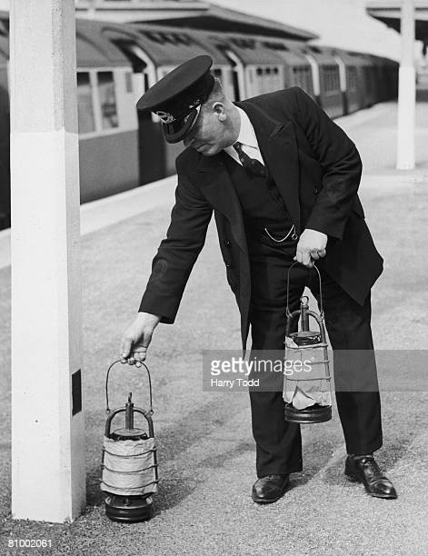 London Underground worker places covered hurricane lamps on the platform at an open-air tube station, London, 16th September 1939. The lamps are for...