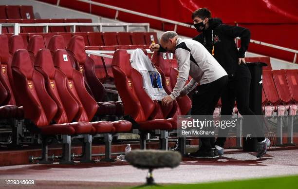 London United Kingdom 29 October 2020 Dundalk kitman Noel Walsh accompanied by his son Darragh places a jersey in the team dugout in commemoration to...