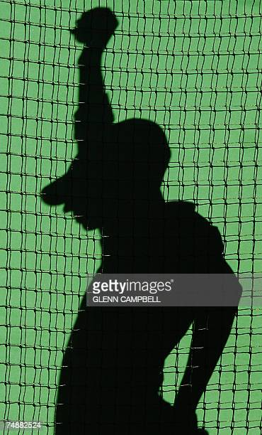 A ballboy's shadow is seen on a wall of number one court during the first round of the Wimbledon Tennis Championships between Justine Henin of...