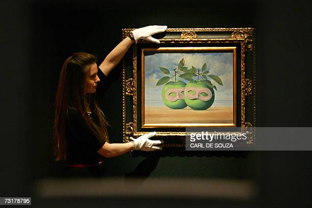 A Christies auction house employee arranges a painting entitled 'La Pretrie Marie' by Belgian artist Rene Magritte during a photocall at the auction...