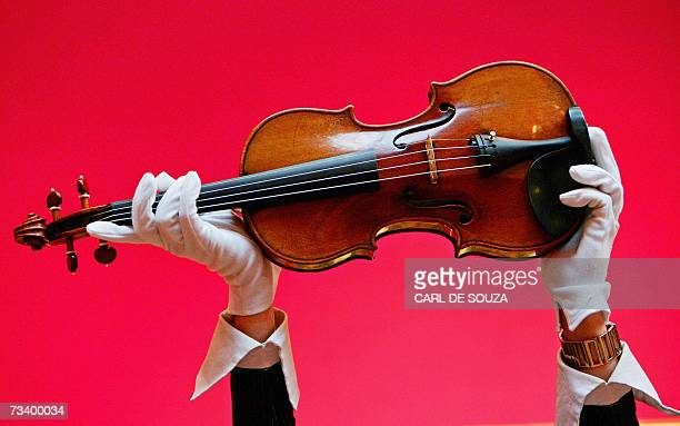 A Christies auction house employee holds up a 1729 Stradivari violin known as the 'Solomon ExLambert' at the auction house in central London 23...