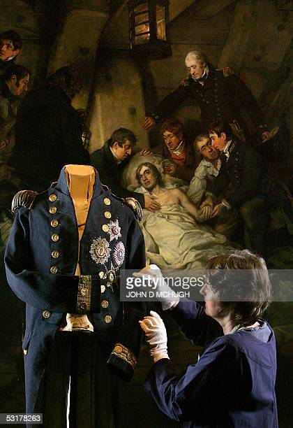 London, UNITED KINGDOM: A curator adjusts the uniform of Horatio Nelson in the National Maritime Museum in London, 01 July in front of the painting...