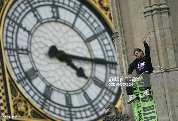 London, UNITED KINGDOM: A protestor from father's 4 justice waves from the roof of the House of Parliament in London, 27 September 2005 after scaling...