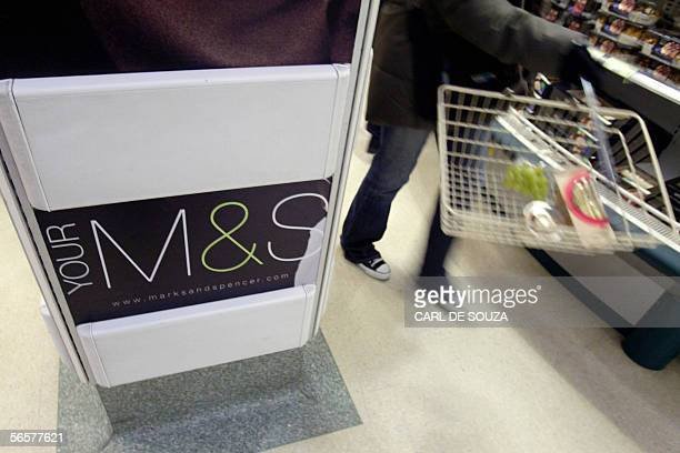 A shopper walks past a Marks and Spencer sign at a store at Covent garden London 12 January 2006 Marks and Spencer the British clothingtofood...