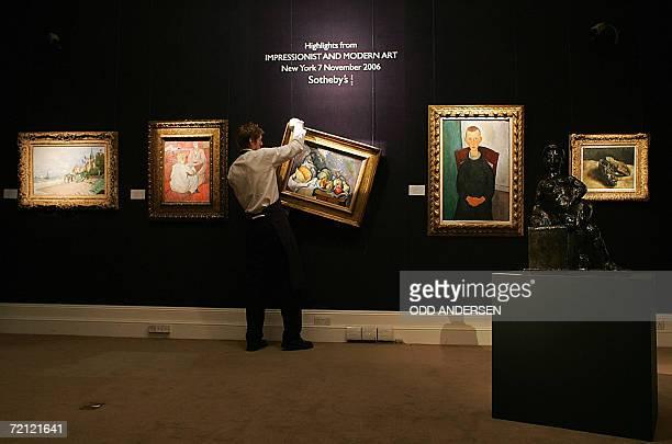 A Sotheby's auction house porter hangs a painting entitled 'Nature morte aux fruits et pot de gingembre' by Paul Cezanne which is valued at 2835m USD...