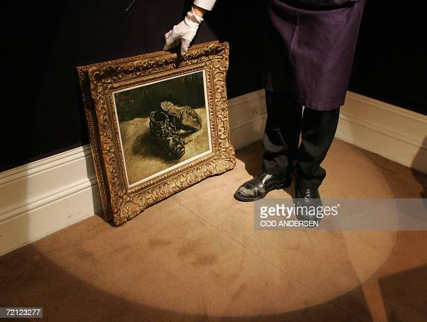 A Sotheby's auction house porter picks up a painting entitled 'A pair of shoes' by Vincent Van Gogh at the auction house gallery in London09 October...