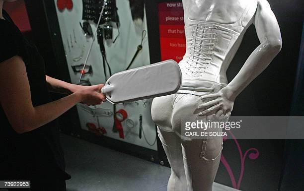 An employee demonstrates an interactive spanking feature at Amora Sex Acadamy a new attraction about sexual relationships London 19 April 2007 Amora...