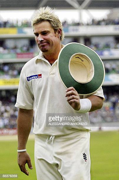 An unhappy Shane Warne leaves the field as England's batsmen take the bad light option for the second time in the afternoon session on the fourth day...