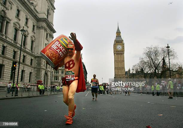 London, UNITED KINGDOM: An unidentified runner dressed in a novelty costume runs with an oversized can of baked beans passes Big Ben as he makes his...