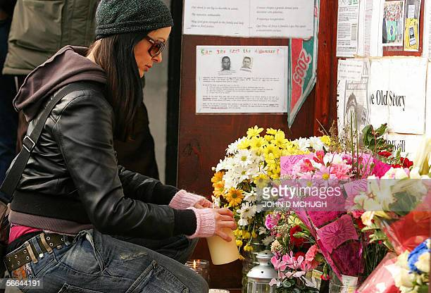 An unidentified woman lights a candle at Stockwell tube station in London 22 January 2006 ahead of a vigil to mark six months since the killing of...