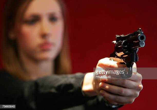 Anna Austen a porter at Bohams auction house holds a Colt Python 357 Magnum Revolver during a preview for a vintage fire arms sale in London 22 March...