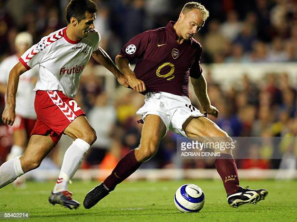 Arsenal's Dennis Bergkamp shrugs off a challenge from Selver Hodzic of FC Thun to shoot and score the winning injurytime goal during the Champions...