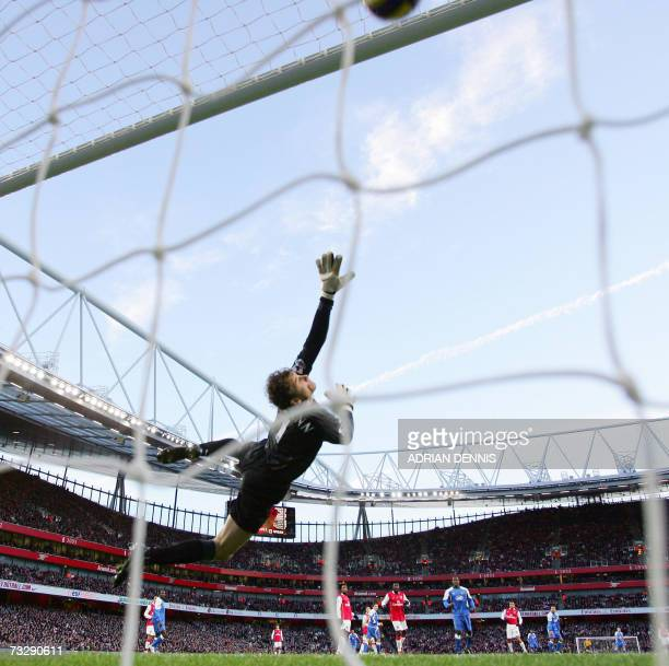 Arsenal's goalkeeper Jens Lehmann dives in vain as the ball hits the roof of the net from a shot from Wigan's Denny Landzaat to score the opening...