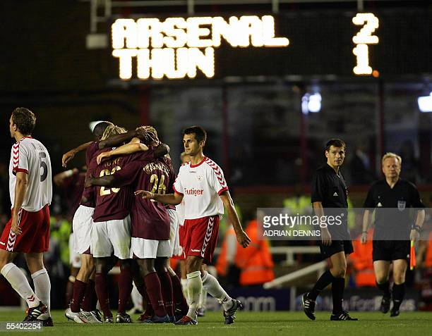 Arsenal's players hug Dennis Bergkamp at the final whistle after he scored the winning injurytime goal against FC Thun during the Champions League...