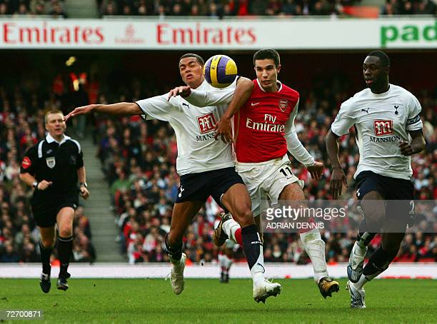 Arsenal's Robin van Persie is challenged by Tottenham Hotspur's Jermaine Jenas and Ledley King while referee Graham Poll follows behind during their...