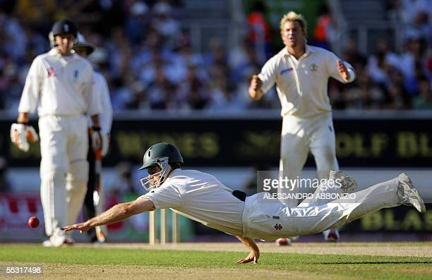 Australia's Simon Katich dives for a catch off the bat of England's Andrew Strauss as bowler Shane Warne appeals on the first day of the fifth and...