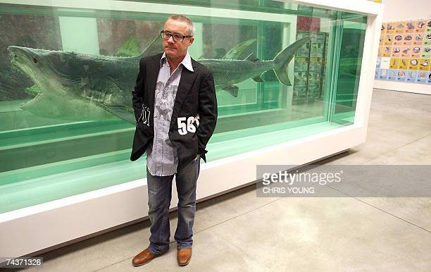 British artist Damien Hirst poses during a photo call with a work entitled 'Death Explained' a divided shark in a formaldehyde solution at the White...