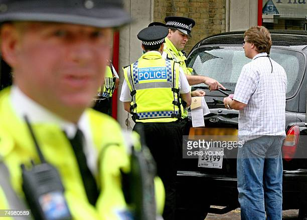 British policemen check the permit papers of a London taxi driver as he approaches Charing Cross railway station in central London 02 July 2007...