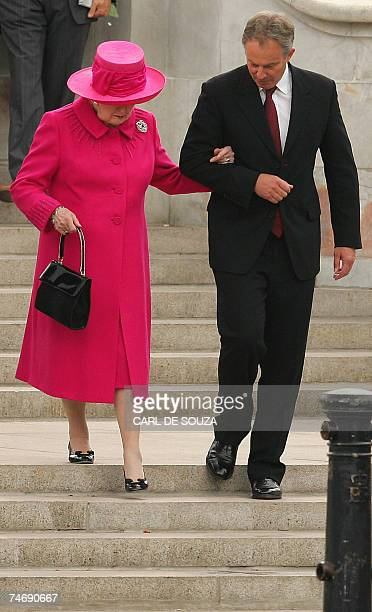 British Prime Minister Tony Blair helps former Prime Minister Margaret Thatcher down the stairs at the Queen Victoria Memorial during a Falklands War...