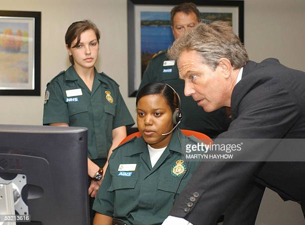 British Prime Minister Tony Blair is shown the ambulance call system by Lisa Andrew at the London Ambulance Services HQ 08 July 2005 Blair toured the...