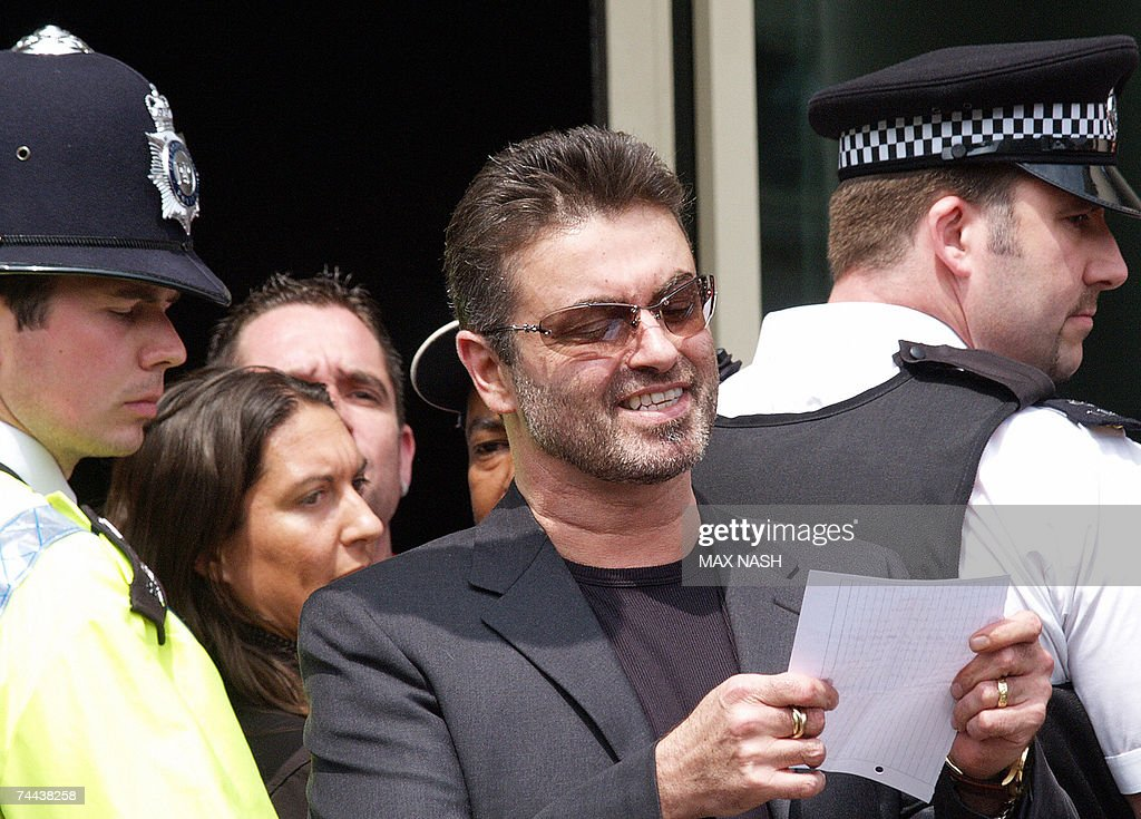 British singer George Michael reads a statement as he leaves the Brent Magistrates Court in London, 08 June 2007, after receiving 100 hours of community service, a two year driving ban, and a two and a half thousand pound fine for driving offenses. A smiling Michael, wearing a charcoal grey suit and a black T-shirt, emerged from the courthouse and read a brief statement before being driven off. 'Just listen to this as I haven't had a chance legally to say anything for the last eight months,' he told reporters. 'I would simply ask people to understand that the media coverage of this case has been farcical, concentrating almost entirely on the prosecution's allegations. AFP Photo/Max Nash