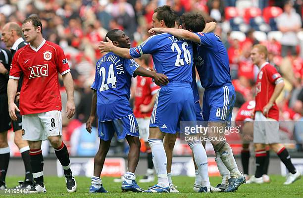 Chelsea players celebrate as Manchester United's Wayne Rooney walks off the field after Chelsea beat Manchester United 10 at Wembley Stadium in...