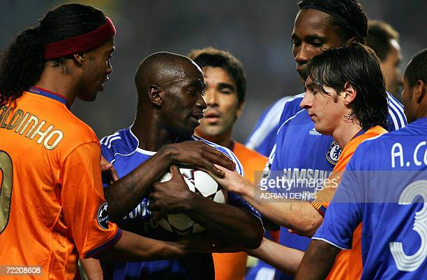 Chelsea's French midfielder Claude Makelele holds onto the ball while being surrounded by Barcelona's Brazilian striker Ronaldinho and Argentinian...
