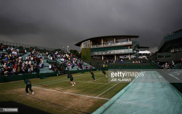 Grounds men pull the cover on the court number 2 as the rain brings play to a halt for a fifth time at the Wimbledon Tennis Championships in...