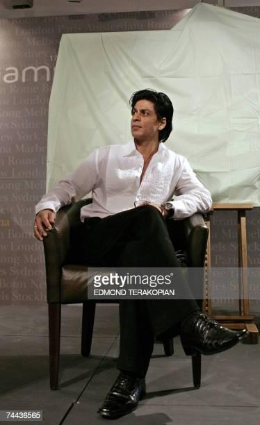 Indian Bollywood actor Shah Rukh Khan poses as 92yearold Indian artist Maqbool Fida Husain paints at Bonhams' Art For Freedom in London 07 June 2007...