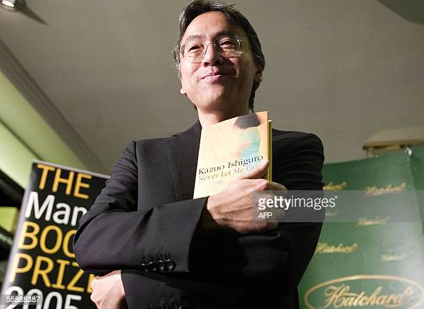 Kazuo Ishiguro poses with his book at Hatchards book store in London 10 October 2005 prior to the announcement of the winner of the The Man Booker...