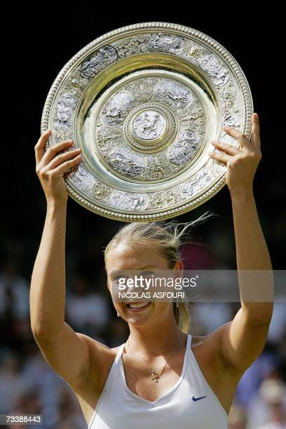 Maria Sharapova of Russia holds up her trophy after her ladies' singles final match with Serena Williams of the US at the 118th Wimbledon Tennis...