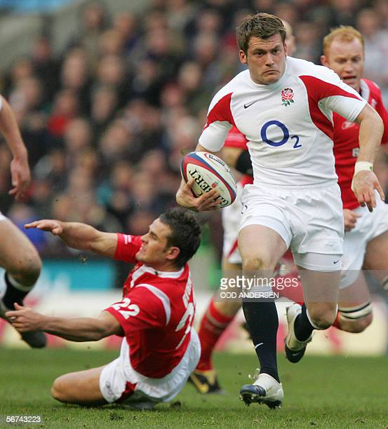 Mark Cueto of England breaks a tackle from Lee Byrne of Wales to score a try during a 6 Nations rugby union match at Twickenham in west London 04...