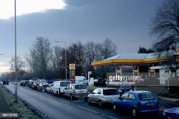 Motorists queue for fuel at a local fuel service station as black smoke from Buncefield oil distribution depot near Hemel Hempstead in Hertfordshire...