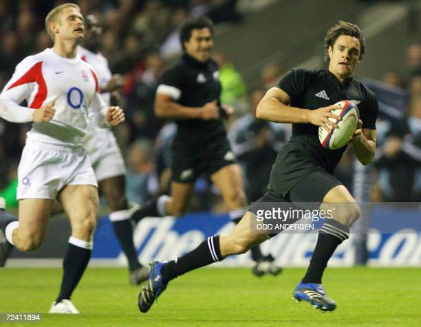 New Zealand All Blacks flyhalf Dan Carter outruns England fullback Iain Balshaw to score a try during their international rugby union test match at...