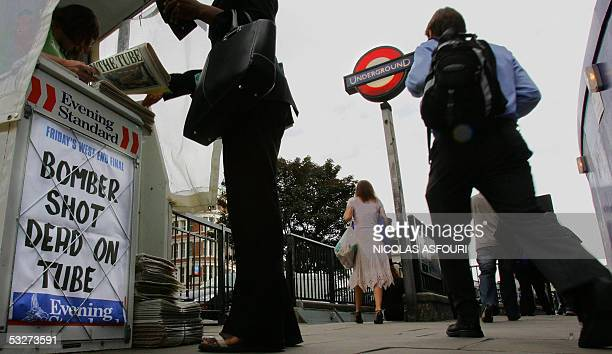 """London, UNITED KINGDOM: People pass by the Evening Standard newspaper's headline, """"BOMBER SHOT DEAD ON TUBE"""" as they make their way to Blackfriars..."""