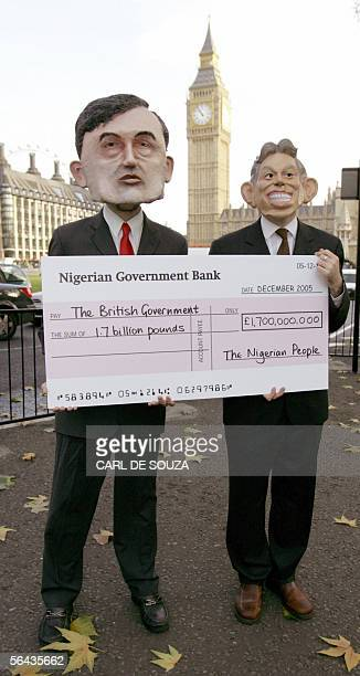 Protesters wearing a Britain's Chancellor of the Exchequer Gordon Brown and and Prime minister Tony Blair masks stand with a cheque in front of the...