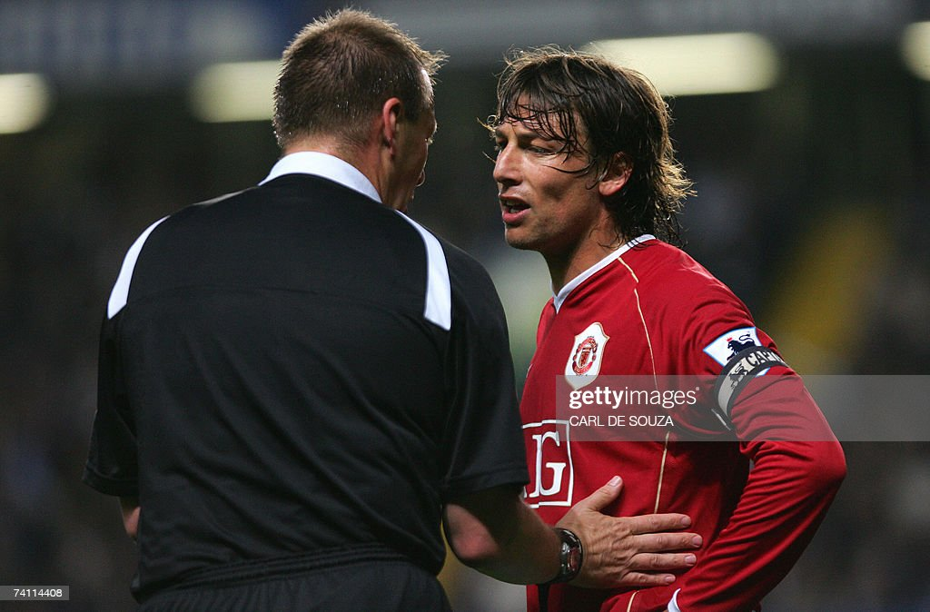 Referee Graham Poll (L) tries to calm do... : News Photo