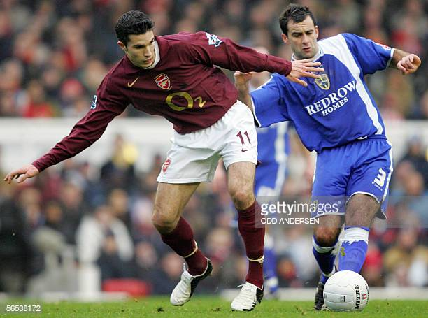 Robin Van Persie of Arsenal vies for the ball with Chris Barker of Cardiff City during a third round FA cup match at Highbury in north London 07...