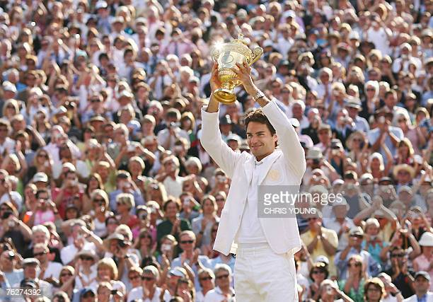 London, UNITED KINGDOM: Roger Federer of Switzerland shows the trophy after defeating Rafael Nadal of Spain during the final of the Wimbledon Tennis...