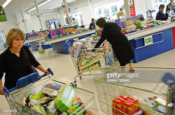 Shoppers at the Osterley branch of Tesco in London wheel their goods past the checkouts 03 October 2006 British supermarket giant Tesco revealed...
