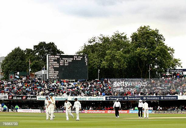 London, UNITED KINGDOM: The Lords crowd puts up their umbrellas as the teams leave the pitch for a further rain interruption during the third of the...